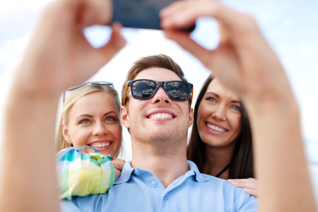 summer, holidays, technology, vacation and happiness concept - group of friends taking picture with smartphone camera photo