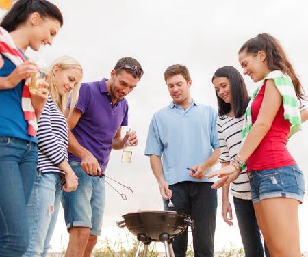 Sommer, Ferien, Urlaub, glückliche Menschen Konzept - Gruppe von Freunden, die Picknick machen und Barbecue am Strand Standard-Bild