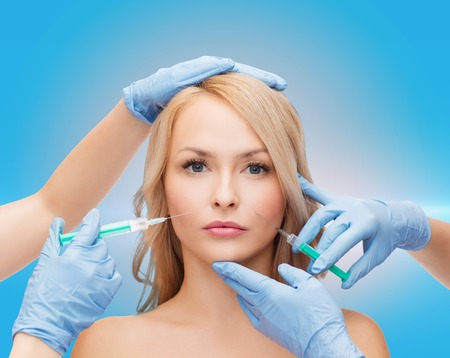 beauty and cosmetic surgery concept - woman face and beautician hands with syringes photo