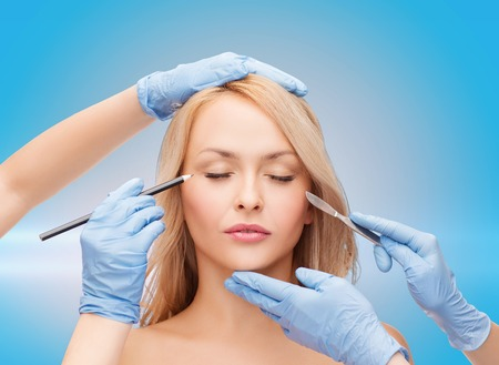 laser surgery: healthcare, beauty and medicine concept - beautiful woman face with closed eyes and beautician hands with pencil and scalpel Stock Photo