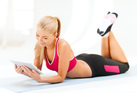 fitness, technology and exercise concept - smiling woman lying on the floor and looking into tablet pc computer Stock Photo