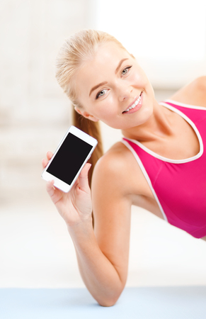 fitness, technology, advertiding and exercise concept - smiling woman lying on the floor and sowing smartphone blank black screen photo