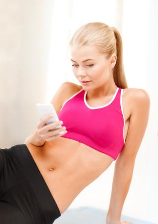 fat burning: fitness, technology and exercise concept - smiling woman sitting on the floor and looking into smartphone