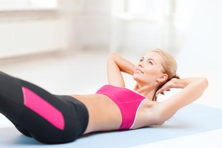 sit ups: fitness and exercise concept - beautiful sporty woman doing exercise on the floor Stock Photo