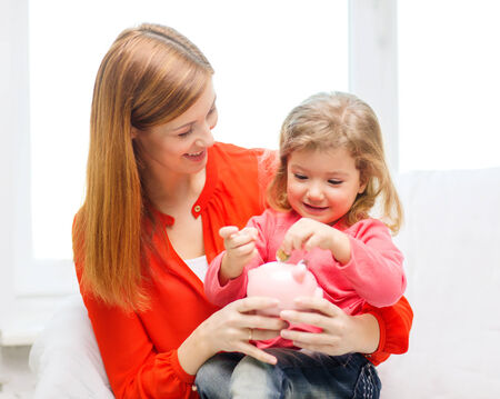 investmen: family, children, money, investmen and happy people concept - happy mother and daughter with small pink piggy bank Stock Photo