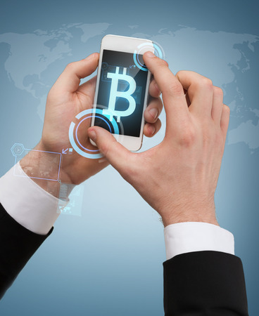 business, internet and technology concept - businessman touching screen of smartphone with bitcoin sign on screen photo