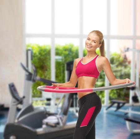 hula: fitness ang gym concept - young sporty woman with hula hoop at gym