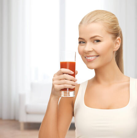 heath and diet concept - young woman holding glass of tomato juice Stock Photo
