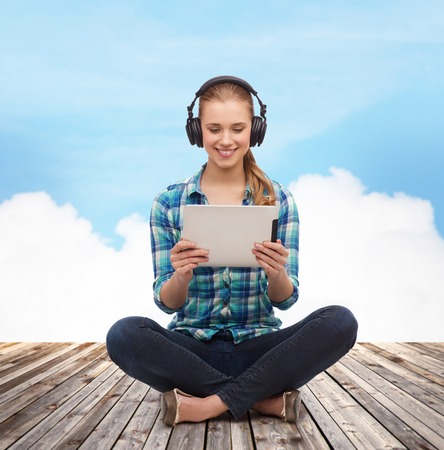 watching movie: technology, internet and people concept - smiling young woman in casual clothes sitiing on floor with tablet pc computer and headphones