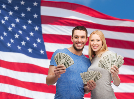 finance, money and family concept - smiling couple holding dollar cash money