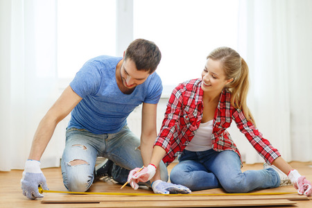 repair, building and home concept - smiling couple measuring wood flooring photo
