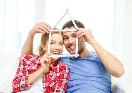 metro medir: pareja sonriente con la casa de la cinta de medir en la nueva casa - en movimiento, el hogar y concepto de pareja
