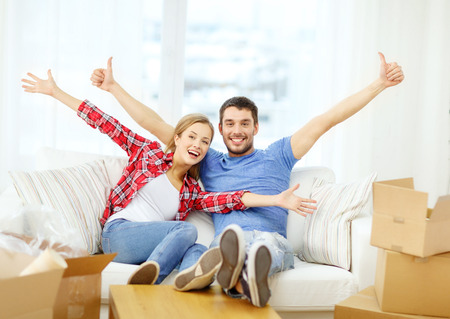 welcome home: moving, home and couple concept - smiling couple relaxing on sofa in new home Stock Photo