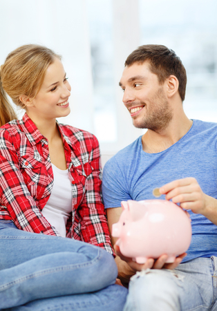 money, home, finance and relationships concept - smiling couple with piggybank sitting on sofa Stock Photo