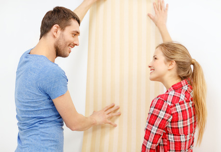 repair, interior design, building, renovation and home concept - smiling couple choosing wallpaper for new home