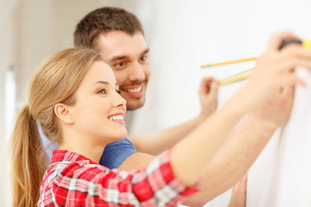 metric: repair, building and home concept - smiling couple measuring wall
