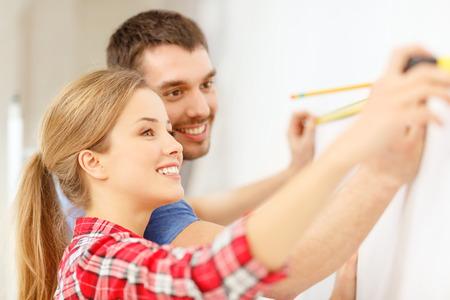 cintas metricas: reparación, construcción y concepto de hogar - sonriente pareja medición de la pared
