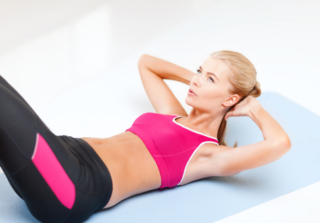 exercice: fitness and exercice concept - beautiful sporty woman doing exercise on the floor