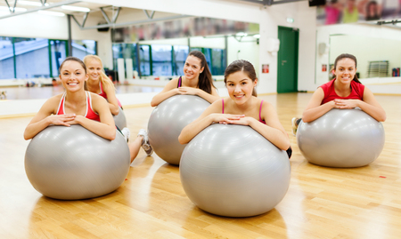 fit ball: fitness, sport, training, gym and lifestyle concept - group of smiling people working out in pilates class Stock Photo