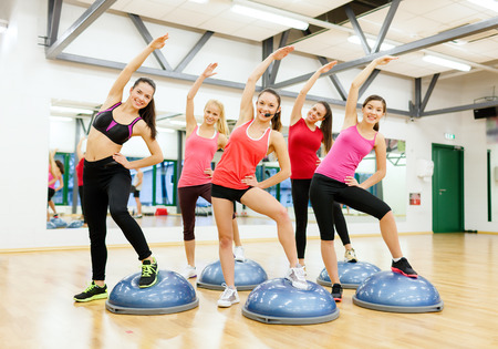 half ball: fitness, sport, training, gym and lifestyle concept - group of smiling female doing aerobics with half ball,
