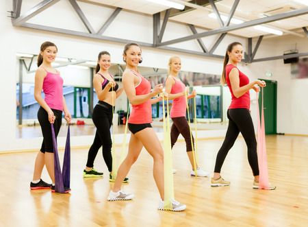 rubber bands: fitness, sport, training, gym and lifestyle concept - group of smiling people with instructor working out with rubber bands in the gym