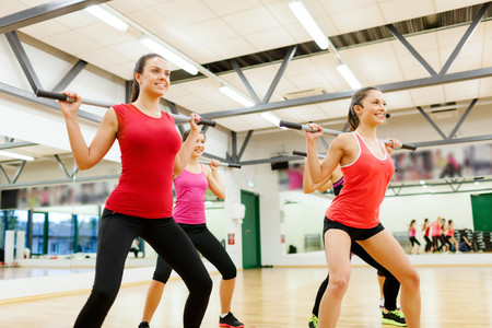 gym class: fitness, sport, training, gym and lifestyle concept - smiling trainer in front of the group of people working out with barbells in the gym
