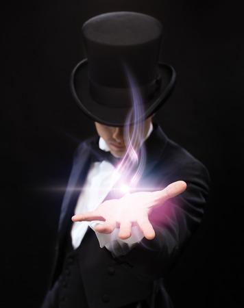 Concepto de magia, rendimiento, circo, espectáculo y publicidad: mago sosteniendo algo en la palma de su mano Foto de archivo