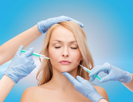 beauty and cosmetic surgery concept - woman with closed eyes and beautician hands with syringes photo