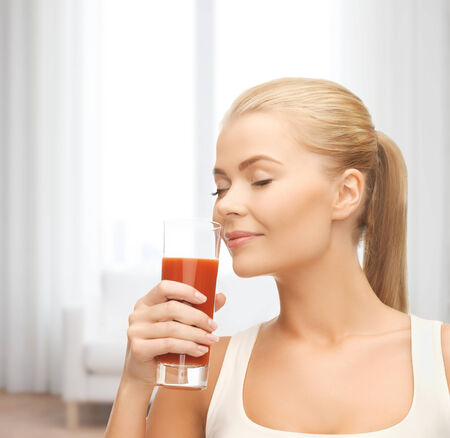 health, diet and food concept - close up of young woman drinking tomato juice photo