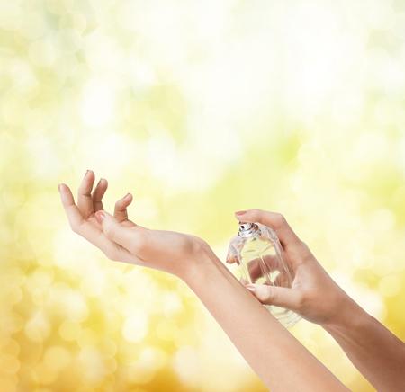 fragranza: cosmetici, parti del corpo e il concetto di bellezza - close up di mani di donna spruzzare profumo