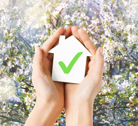 real estate and family home concept - hands holding paper house with green check mark photo