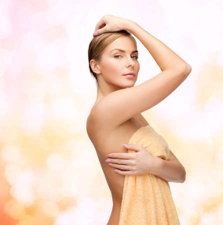 golden shower: health and beauty concept - beautiful woman in towel