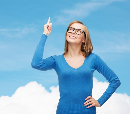advertisement concept - attractive young woman in casual clothes and black eyeglasses pointing her finger up photo
