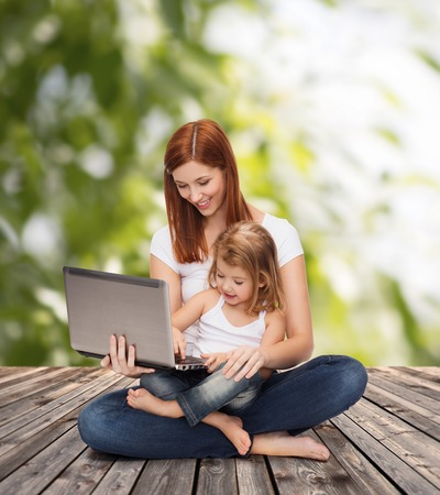childhood, parenting and technology concept - happy mother with adorable little girl with laptop photo