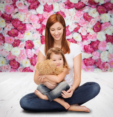 childhood, parenting and relationship concept - happy mother with adorable little girl and teddy bear photo