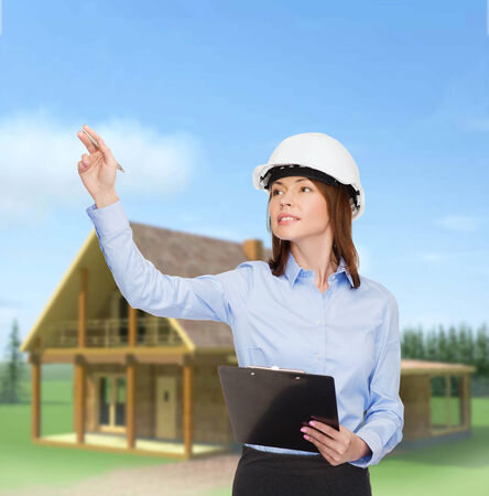building, developing, consrtuction and architecture concept - smiling businesswoman in white helmet with clipboard pointing finger photo