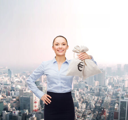 business and money concept - young businesswoman holding money bags with euro photo