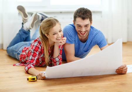 blueprint house: repair, building, renovation and home concept - smiling couple looking at blueprint at home