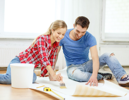 repair, building and home concept - smiling couple smearing wallpaper with glue photo