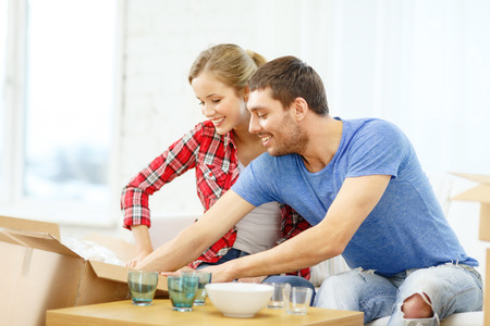 moving activity: repair, building and home concept - smiling couple unpacking kitchenwear