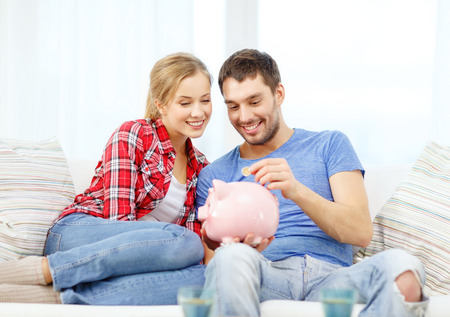 money, home, finance and relationships concept - smiling couple with piggybank sitting on sofa Imagens