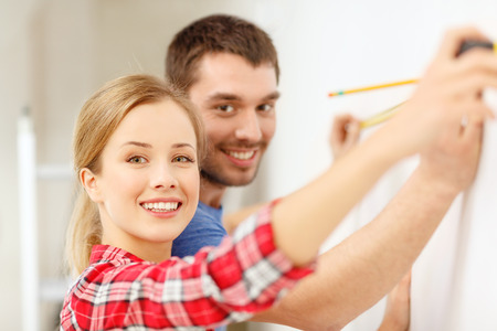 repair, building and home concept - smiling couple measuring wall photo