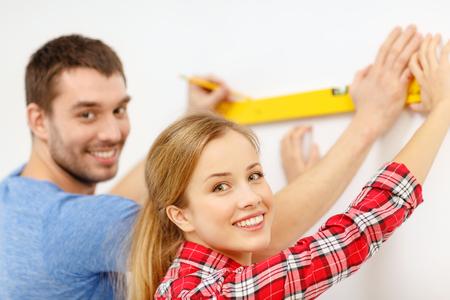 metro medir: reparación, construcción y concepto de hogar - sonriente pareja nuevo hogar del edificio utilizando el nivel de burbuja para medir