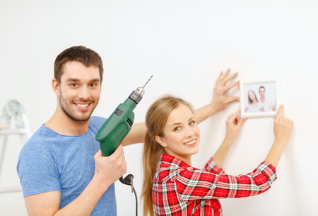 repair, interior design, building, renovation and home concept - smiling couple drilling hole in wall and putting picture up at home photo