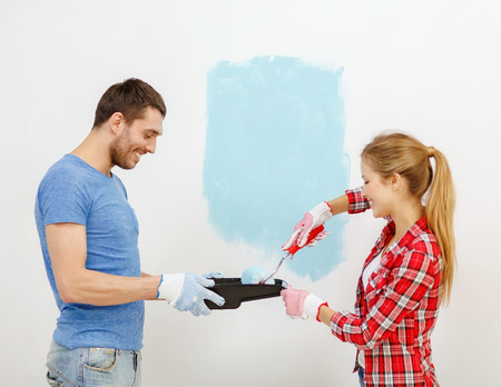 repair, building and home concept - smiling couple painting wall at home photo