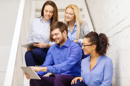 internet education: business, technology and startup concept - smiling creative team with tablet pc computer sitting on staircase