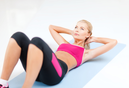 sit ups: fitness and exercice concept - beautiful sporty woman doing exercise on the floor
