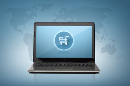 technology, shopping and advertisement concept - laptop computer with shopping cart button on screen photo