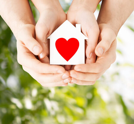 charity  symbol: charity, real estate and family home concept - closeup picture of male and female hands holding white paper house with red heart Stock Photo