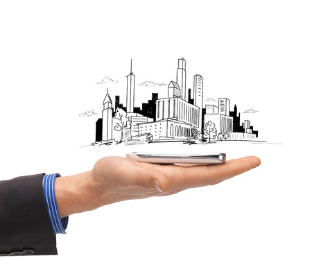 business and architecture concept - close up of man hand with smartphone and city sketch photo